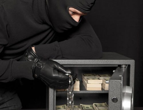 Burglar stealing safe contents